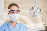 Dentist in surgical mask and protective glasses looking at camera