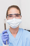 Dentist in blue scrubs holding dental drill