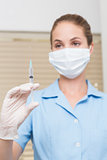 Dental assistant holding injection looking at it