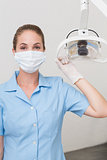 Dental assistant in mask holding light