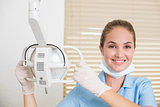 Dental assistant smiling at camera beside light