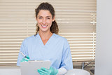 Dentist in blue scrubs writing on clipboard