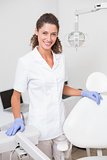 Dental assistant smiling at camera beside chair