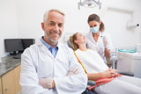 Dentist smiling at camera with assistant and patient behind