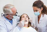 Dentist examining a patients teeth in the dentists chair with assistant