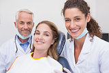 Dentist his assistant and patient all smiling at camera