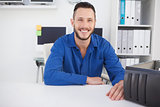 Computer engineer sitting at desk smiling at camera