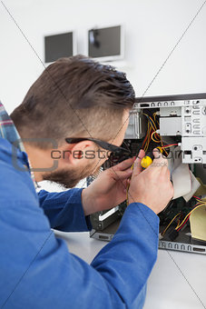 Computer engineer working on broken console with screwdriver