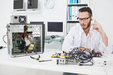 Computer engineer looking at broken device and making a phone call