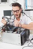Angry computer engineer pulling wires