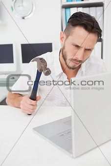 Casual businessman holding hammer over laptop