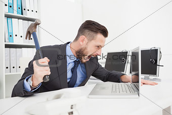Angry businessman holding hammer over laptop