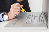 Technician lifting off key with screwdriver on laptop