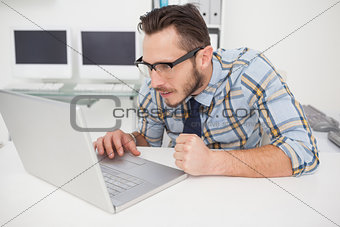 Casual businessman at his desk working on laptop