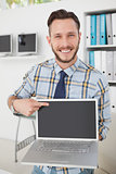 Happy casual businessman pointing to laptop