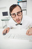 Nerdy shocked businessman working on computer