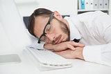 Nerdy businessman sleeping on keyboard