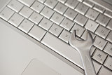 Pliers lying on silver keyboard