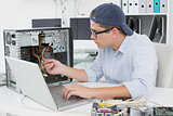 Computer engineer working on broken console with laptop