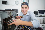 Smiling computer engineer working on broken console with screwdriver