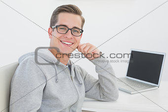 Casual man sitting at desk with laptop