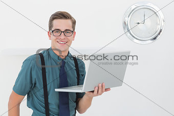 Nerdy businessman holding laptop smiling at camera