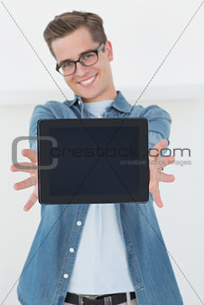 Nerdy businessman showing tablet pc smiling at camera