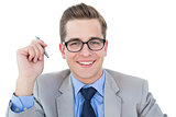 Nerdy businessman holding pen smiling at camera
