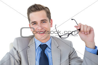 Smiling businessman holding his glasses