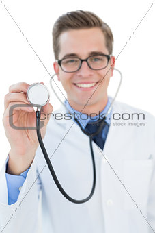 Smiling young doctor holding up stethoscope