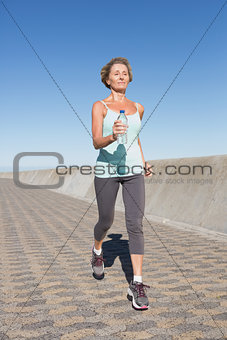 Active senior woman jogging on the pier