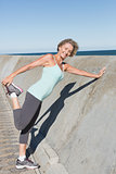Active senior woman stretching on the pier