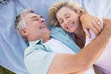 Happy senior couple cuddling on blanket