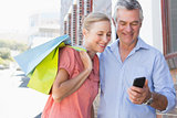 Happy senior couple looking at smartphone holding shopping bags