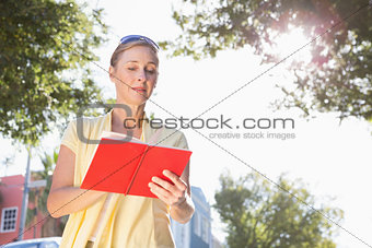 Blonde woman looking at her guide book