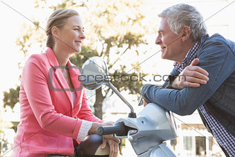 Happy senior couple posing with their moped