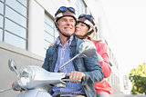 Happy senior couple riding a moped