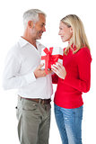 Smiling couple embracing and holding gift