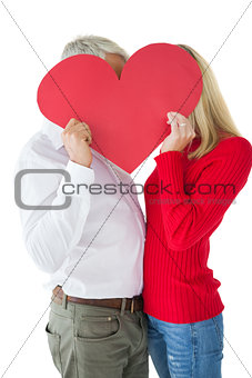 Couple embracing and holding heart over faces