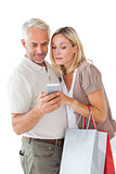 Happy couple holding shopping bags and smartphone