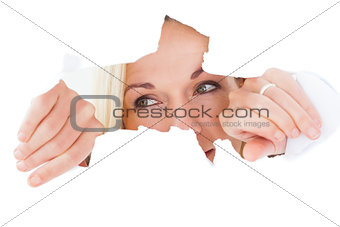Blonde woman looking through torn paper