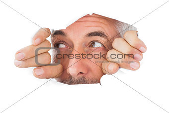 Man looking through torn paper