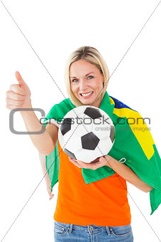 Football fan holding ball and wearing brazil flag