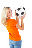 Football fan holding ball in orange tshirt