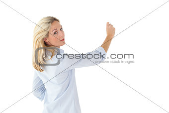 Smiling blonde woman writing and looking at camera