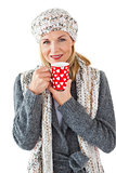 Smiling woman in winter fashion looking at camera with mug