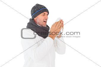 Sick man in winter fashion sneezing