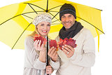 Couple in winter fashion showing autumn leaves under umbrella