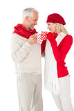Smiling couple in winter fashion toasting with mugs