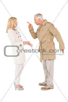 Angry couple fighting in trench coats